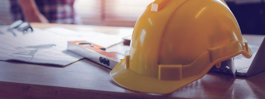 Construction helmet and project plan on a table